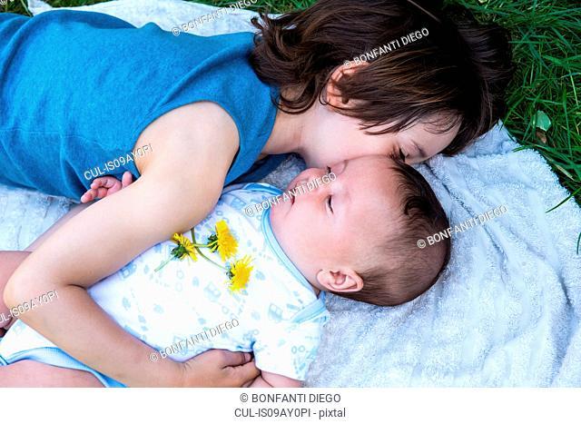 Boy hugging baby brother in garden