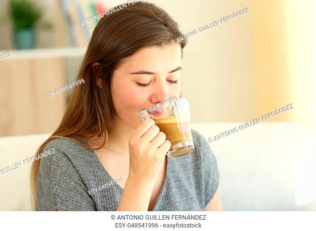 Teen drinking coffee with milk sitting on a couch in the living room at home