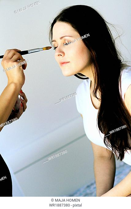 Stylist applying eyeshadow to young woman's face, Copenhagen, Denmark