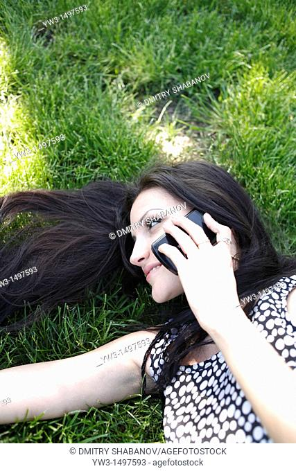 25 year old woman outdoors on the grass with cell phone