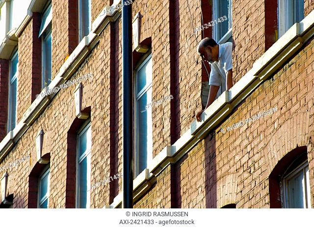 A man leans out the window of a brick residential building looking below; London, England