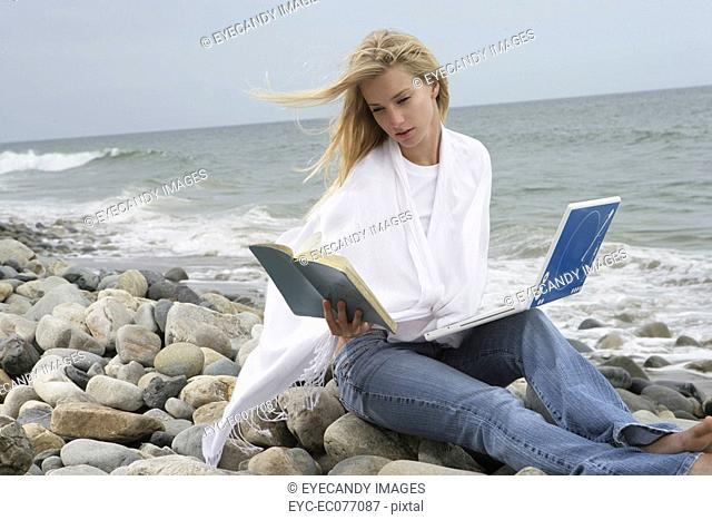 Young woman on beach with book and laptop