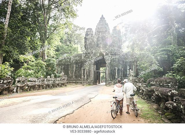 A couple of tourists with bikes in east gate of Angkor Thom compound (Siem Reap Province, Cambodia)