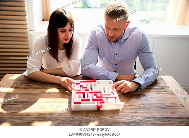 Two Young Businesspeople Solving Maze Puzzle Over Wooden Desk