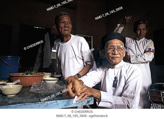 Three senior men sitting in a restaurant, Vietnam