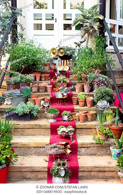 Stairs with little puppets, figurines, flowers and cactuses, arts and crafts on a red carpet in a public garden in Donostia San Sebastian