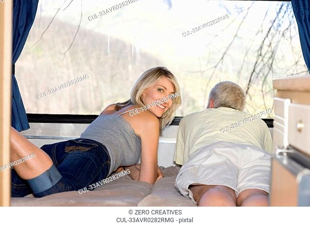 Older couple laying on bed together