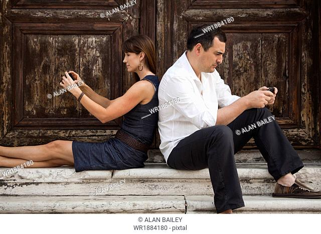 Italy, Venice, Couple sitting on steps, using smart phones