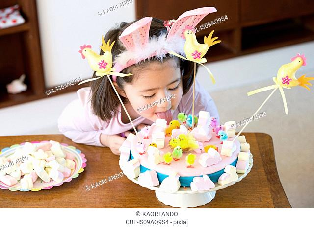 Young girl licking cake on table