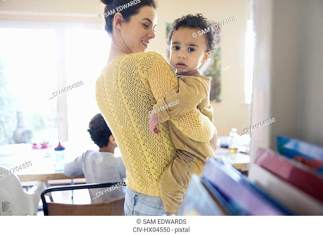 Portrait mother holding curious baby son