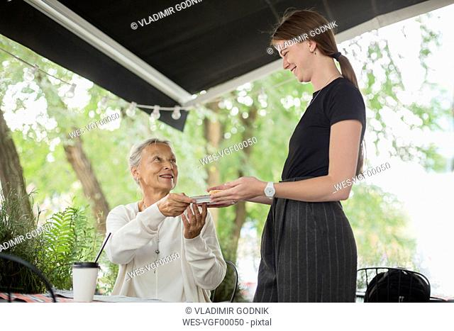 Waitress handing over plate to smiling senior woman at an outdoor cafe