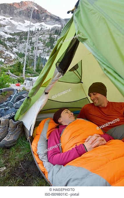 Couple chatting in sleeping bags in tent at Fault Lake, Selkirk Mountains, Idaho