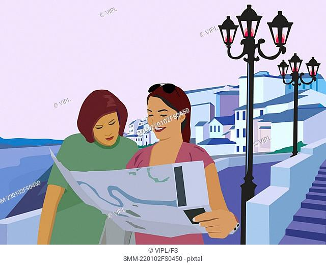 Women reading map and resort in the background