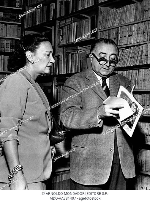 Cesare Branduani with Elsa Merlini. Italian bookseller Cesare Branduani looking through a book in company of Italian singer and actress Elsa Merlini (Elsa...