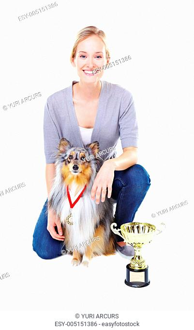 Beautiful young dog owner with her champion shetland sheepdog and a gold trophy