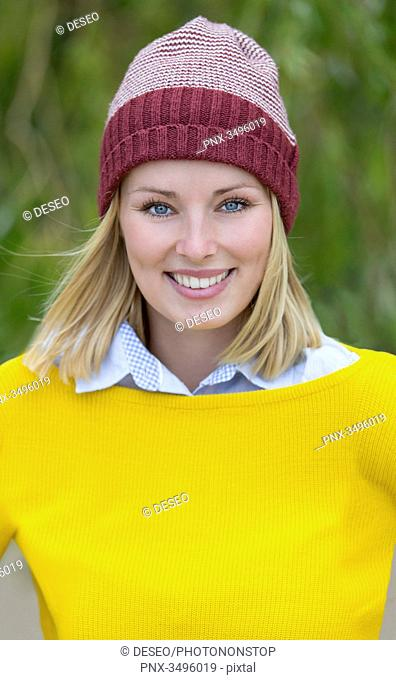 Portrait of a blonde woman in park smiling at camera