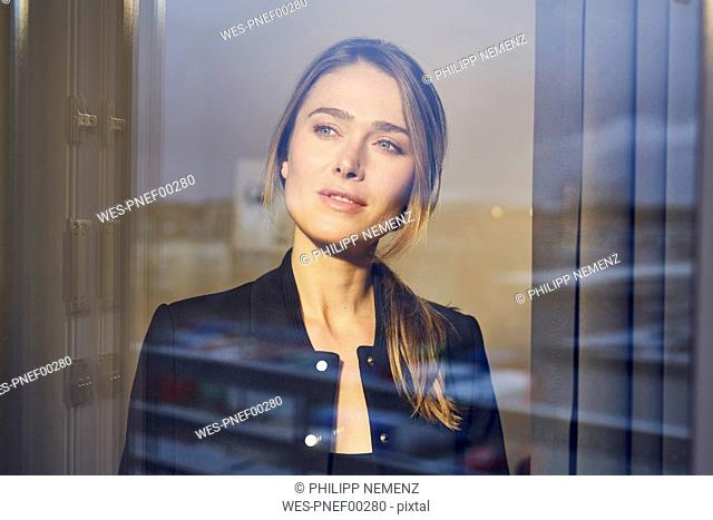 Portrait of businesswoman behind windowpane
