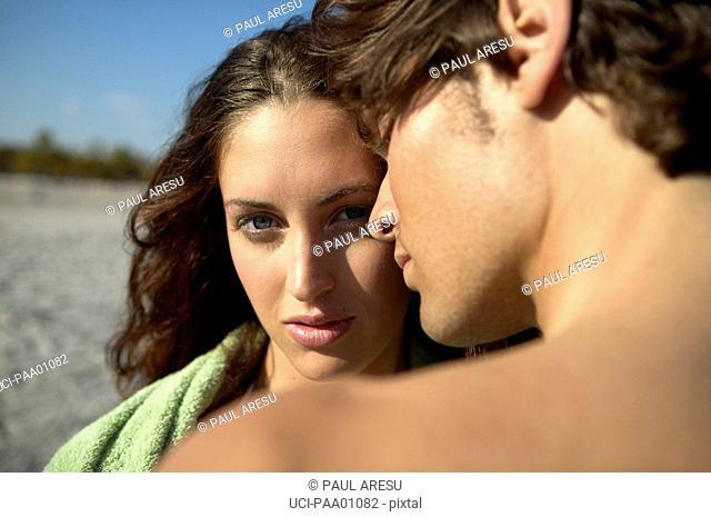 Young Hispanic couple hugging on beach