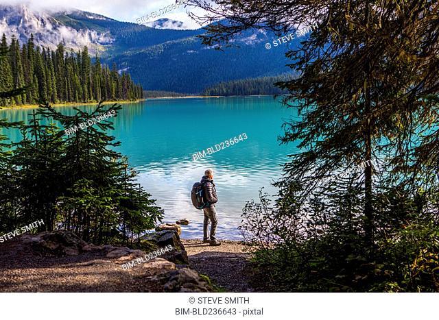 Caucasian man standing at mountain lake
