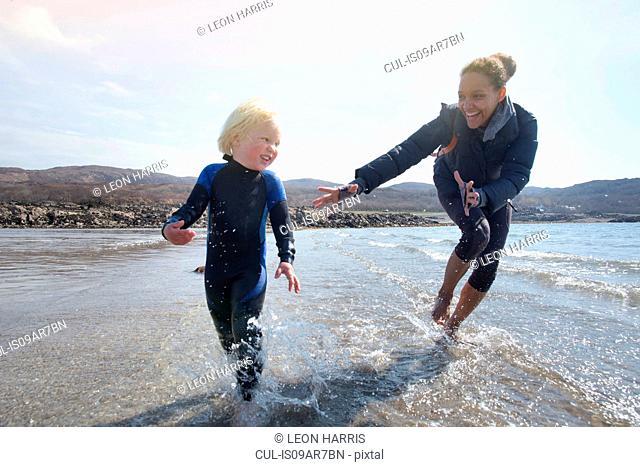 Mother and son running on beach, Loch Eishort, Isle of Skye, Hebrides, Scotland