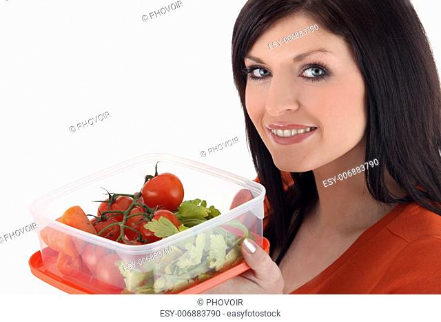 Woman with a plastic lunch box of fresh vegetables