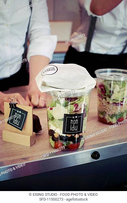 A layered take-away salad on a counter in a food truck