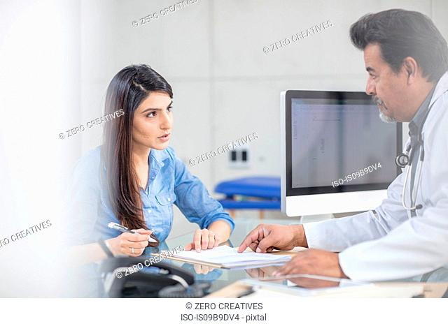 Male and female doctor sitting at table, having conversation