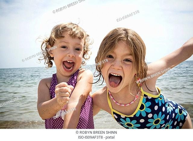 Portrait of two sisters pulling faces on beach at Falmouth, Massachusetts, USA