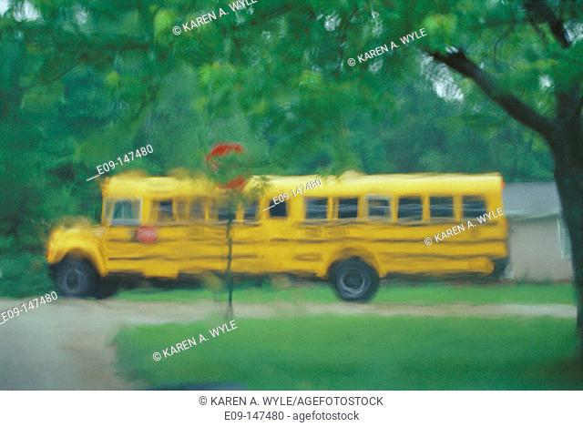 Schoolbus at neighborhood corner, seen through rainy windshield
