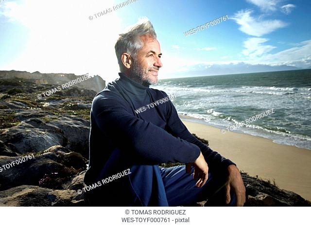 South Africa, portrait of smiling man sitting on rocks at the beach