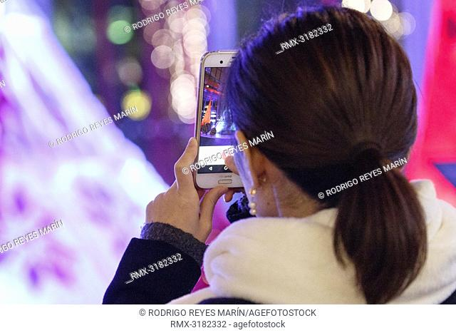 November 15, 2018, Tokyo, Japan - A visitor takes a picture of a huge Christmas tree at Marunouchi Building in Tokyo. The Christmas tree blinks and plays music...