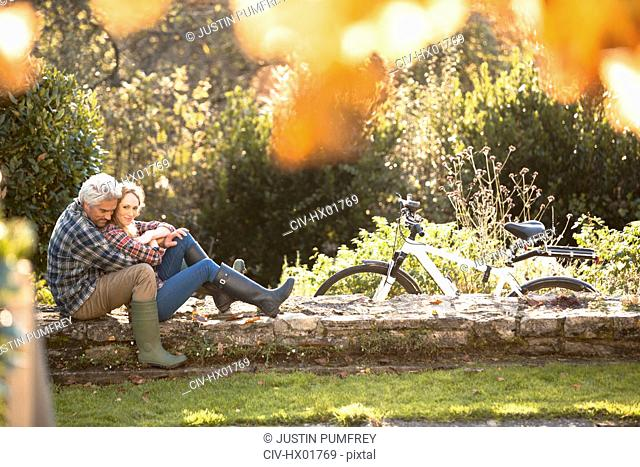 Affectionate couple hugging on stone wall in autumn park