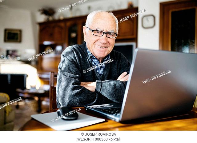 Portrait of smiling senior man with laptop at home