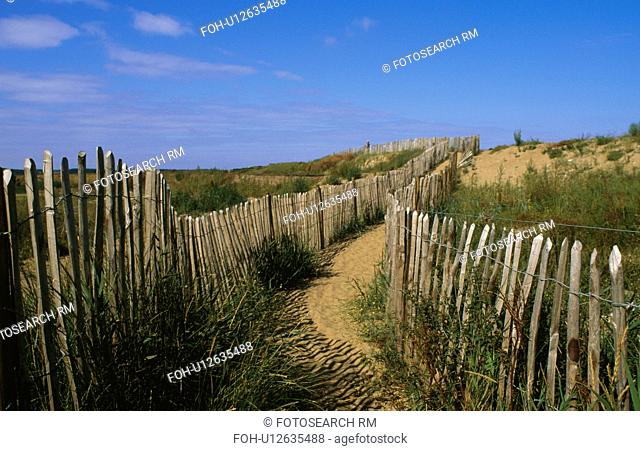 Sandy path between wooden fencing on sand dunes at Holkham beach in Norfolk