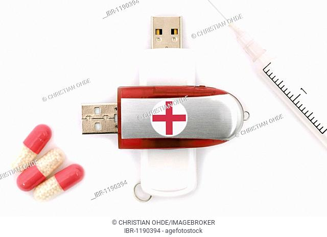 Pen drive with a red cross, injection needle and tablets, symbolic picture for digitalized medical patient data