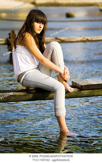 Teenager girl is sitting on an old rotten pier