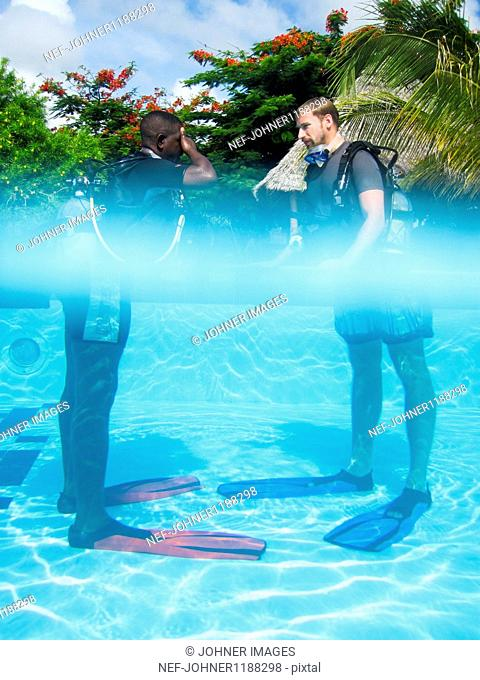 Two tourists with aqualungs in swimming pool