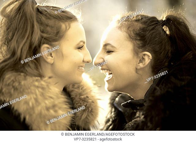 Two young sisters face to face outdoors in sunlight, happy, in Munich, Germany