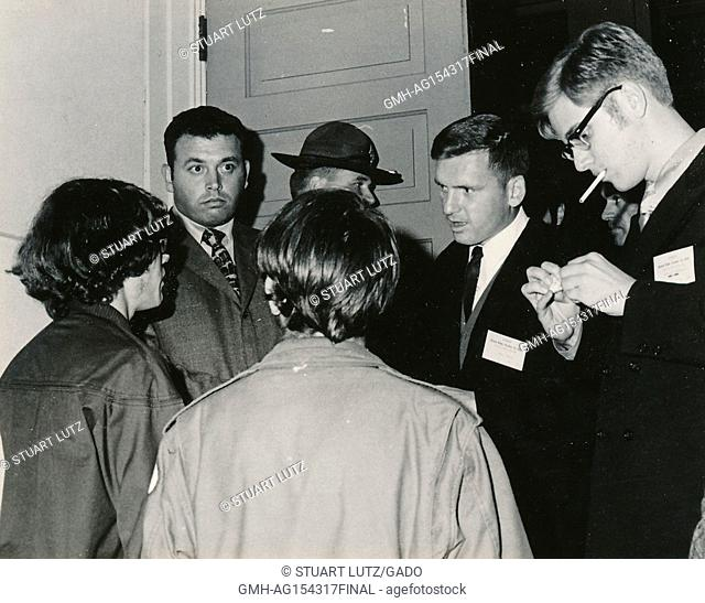 Students wearing hippie attire converse with well-dressed men in suits smoking cigarettes, in a tense scene during an anti Vietnam War student sit-in protest at...