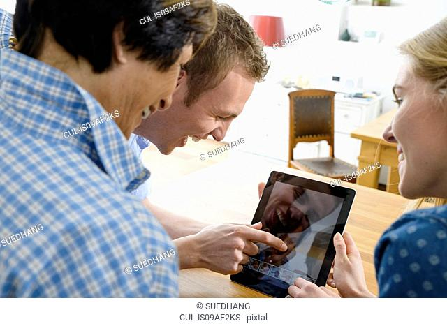 Grandmother and adult grandchildren using distortion on digital tablet
