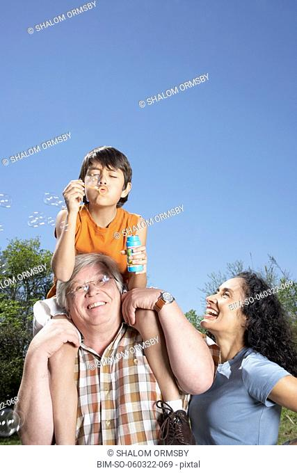 Hispanic grandparents and grandson blowing bubbles outdoors