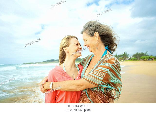 A mother and daughter together on the beach at the water's edge; Kauai, Hawaii, United States of America
