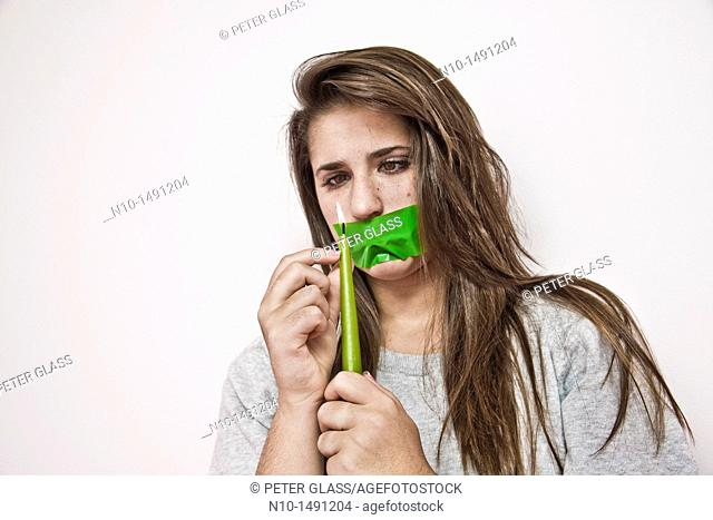 Teen girl with tape over her mouth, holding a lit candle