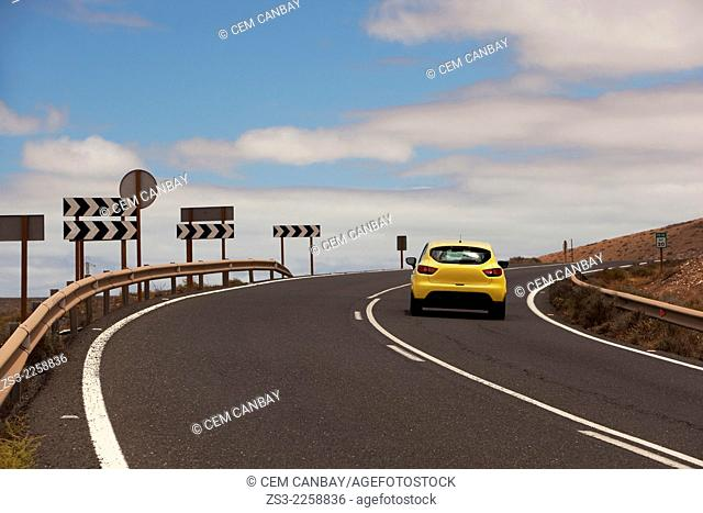 Yellow car on the mountain road with traffic signs by side, Fuerteventura, Canary Islands, Spain