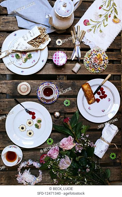 An outdoor table laid with flea market decorations