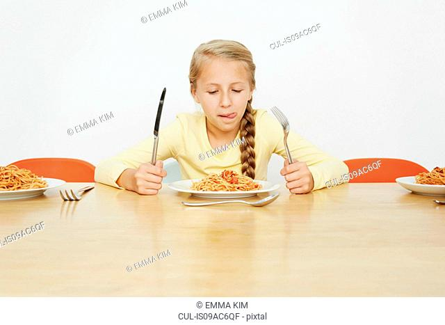 Girl sitting at table with plate full of spaghetti