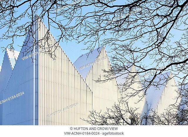 Szczecin Philharmonic Hall, Szczecin, Poland. Architect: Studio Barozzi Veiga, 2014. Tree branches in juxtaposition with zigzag facade