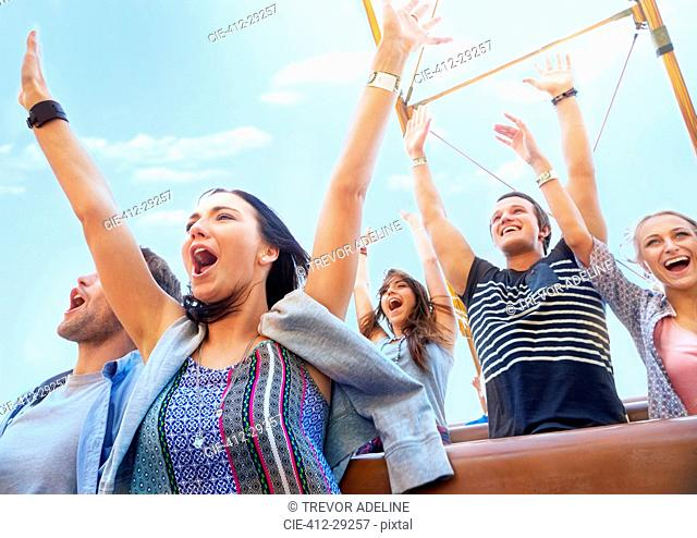 Friends cheering and riding amusement park ride