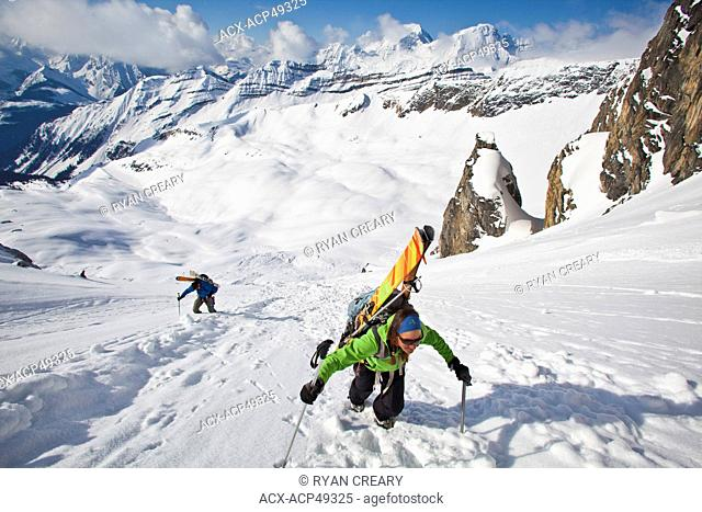 Two backcountry skiers bootpack up a steep face to ski down the other side. Icefall Lodge, British Columbia, Canada