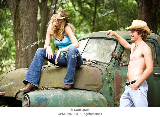 Young cowboy and cowgirl hanging out by vintage truck outdoors